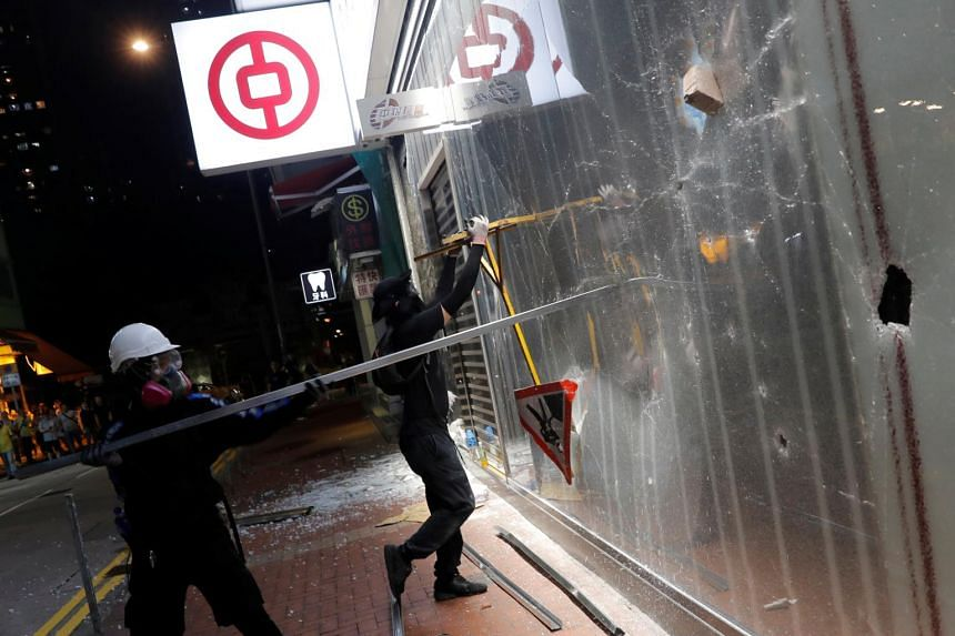 Anti-government protesters vandalise a Bank of China branch during a protest in Tsuen Wan, Hong Kong, on Oct 13, 2019.