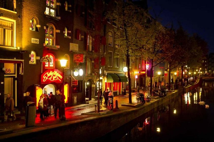 People walk through Amsterdam's red-light district, known as De Wallen, in this file photo taken on Oct 12, 2011.  The Netherlands legalised prostitution in 2000 but concerns have grown about the unchecked growth of the industry.