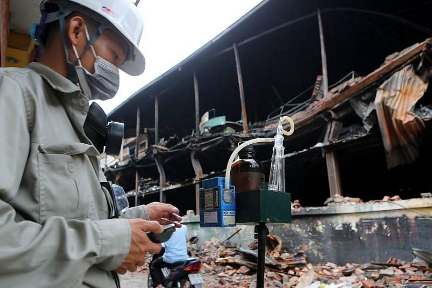 A photo taken on Aug 30 shows a Hanoi Natural Resources and Environment Monitoring official checking for a potential risk of toxin poisoning, following a fire at a light bulb factory.