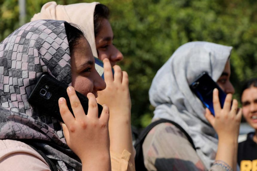 Kashmir youth busy with mobile phones after government authorities lifted the ban on postpaid mobile phones in Kashmir valley, in Srinagar on Oct 14, 2019. Text messaging services were blocked just hours after being restored.