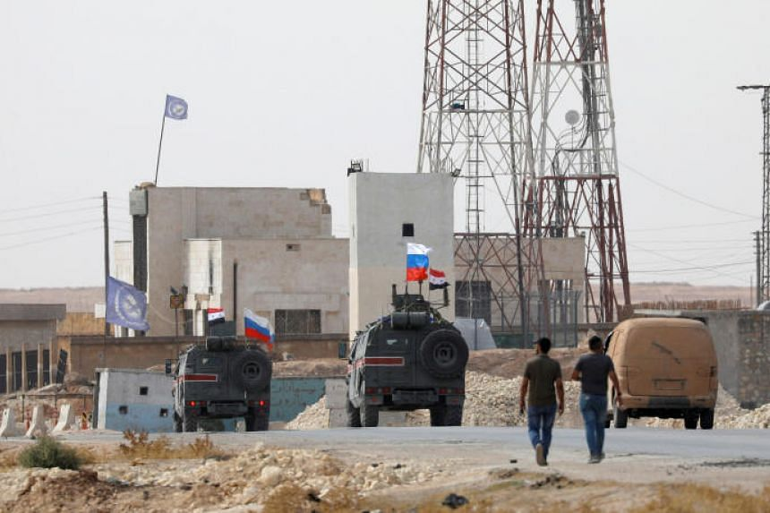 Russian and Syrian national flags are seen on military vehicles near Manbij in Syria on Oct 15, 2019.