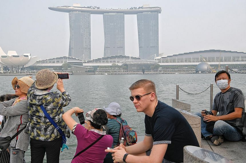 A tourist wearing a mask at the Merlion park on Sept 18. The haze this year was not as bad as the 2015 crisis. In both years, fires were worsened by drier-than-usual weather caused by natural climate phenomena.