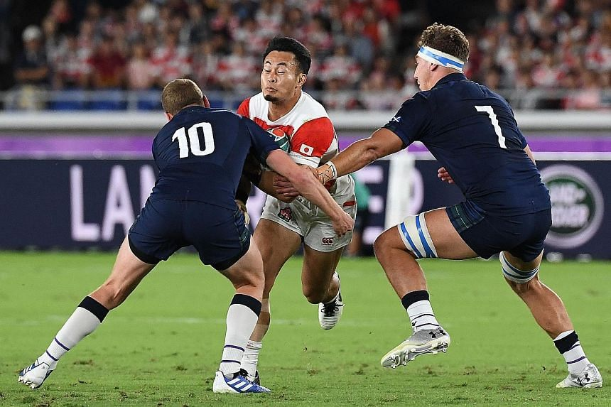 Scotland's Finn Russell (left) and Jamie Ritchie trying to stop Kenki Fukuoka of Japan during their Pool A match last Sunday. Fukuoka scored two tries in the 28-21 win. PHOTO: AGENCE FRANCE-PRESSE