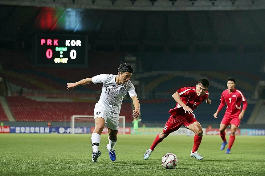 South Korea's Hwang Hee-chan (left) fighting for the ball with North Korea's Kim Chol Bom during their 2022 World Cup qualifier at the Kim Il Sung Stadium in Pyongyang yesterday. The 0-0 draw meant South Korea stayed top of Group H with seven points,