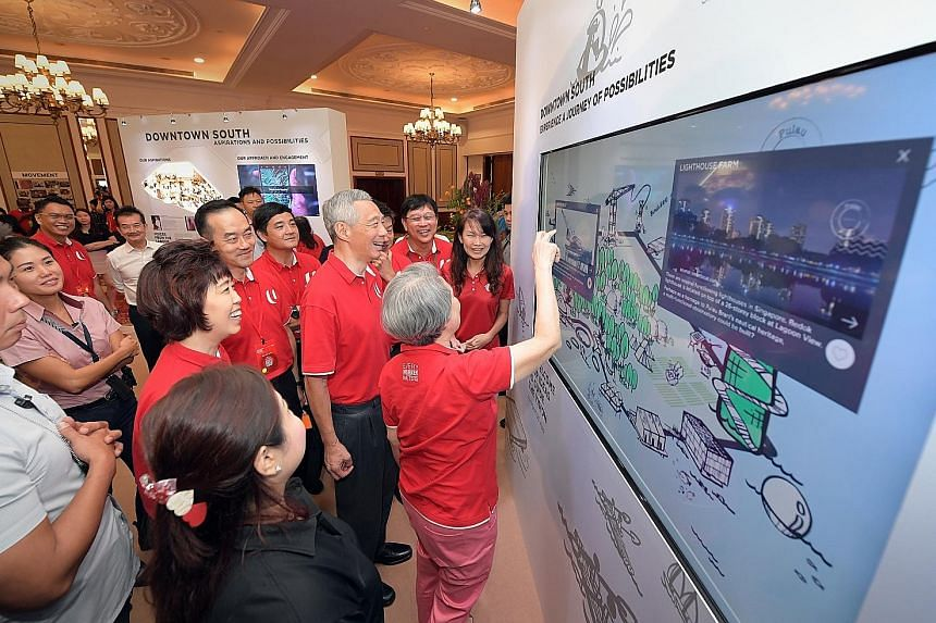 Prime Minister Lee Hsien Loong and his wife, Mrs Lee, viewing the Downtown South display with other guests at the NTUC National Delegates' Conference at Orchid Country Club yesterday.