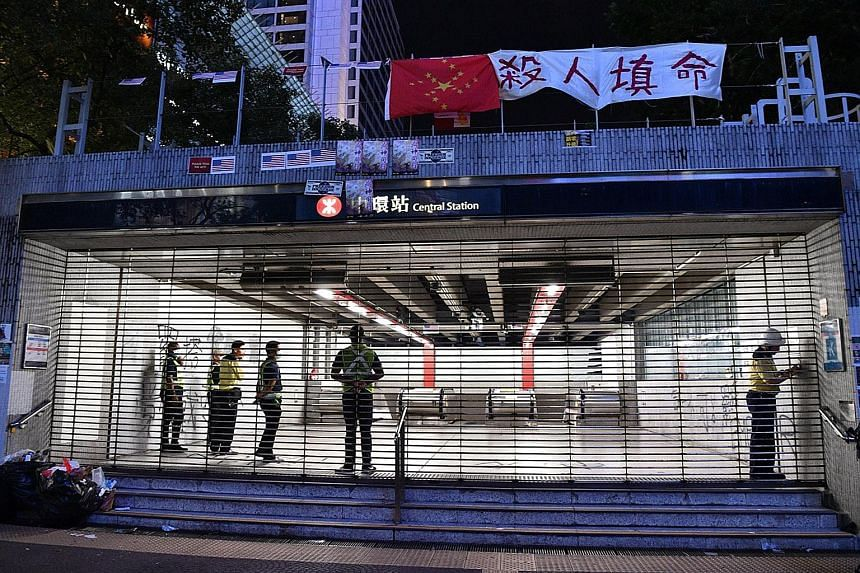 MTR staff closing the shutters at Central Station at 10pm on Monday. Hong Kong's rail system has closed early for more than a week, effectively cutting off the main mode of transportation for millions of residents. The rail operator says it needs ext