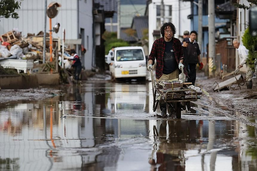 A resident removing muddy items in a flood-hit area in Nagano yesterday. Typhoon Hagibis caused mudslides in 146 places in Japan, while at least 13,000 homes were damaged by flooding. Homes left damaged by the flooding in Nagano, where the embankment