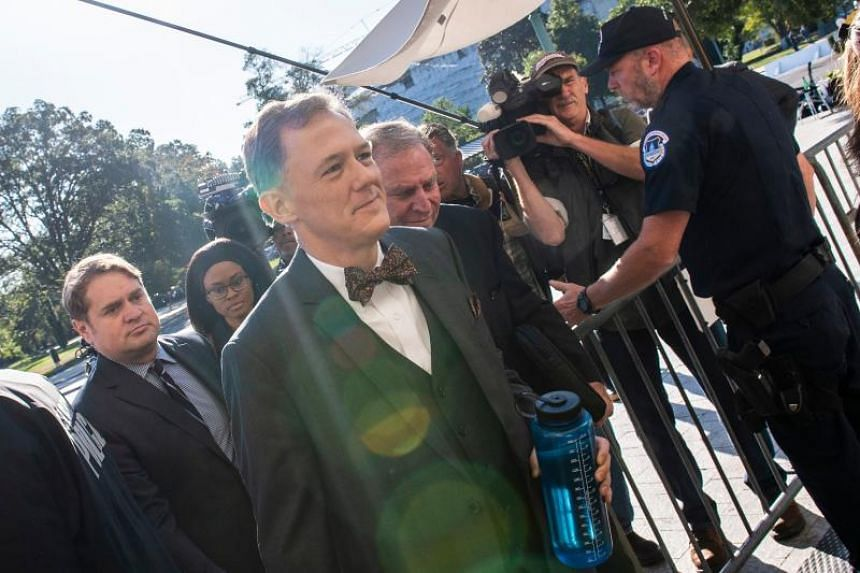 Wearing a bow tie, career diplomat George Kent ignored questions from reporters as he arrived on Capitol Hill to speak with lawmakers behind closed doors on Oct 15.