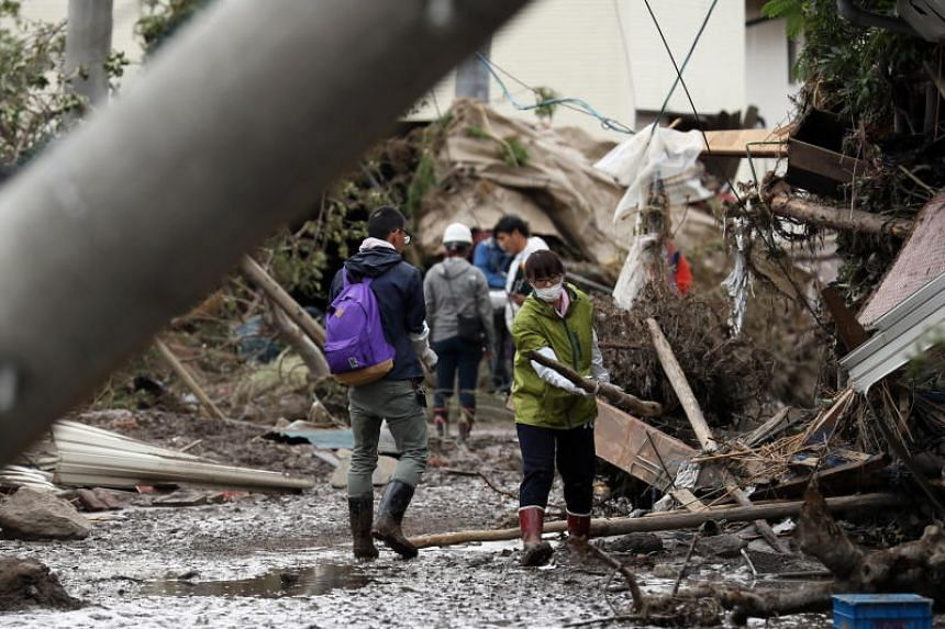 Residents clean a street covered with debris due to the floods in Nagano, Japan, on Oct 15, 2019.