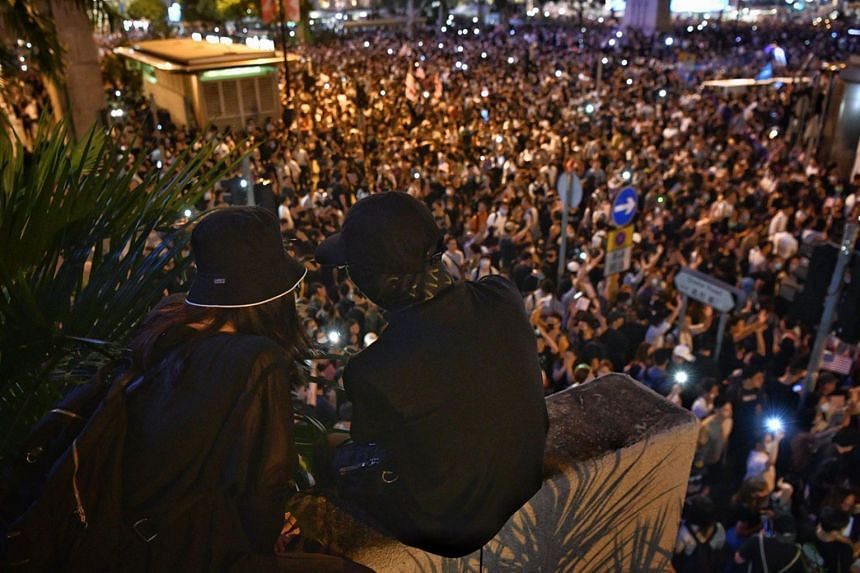 A couple watch as the protesters gather around the roads surrounding Chater Garden in Hong Kong on Oct 14, 2019.
