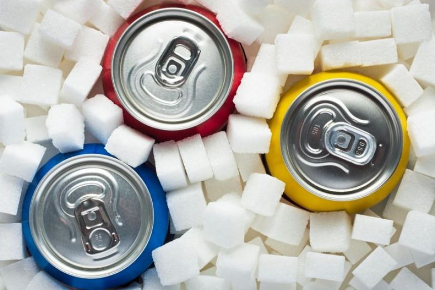 Posed photo showing sugar cubes as background and canned drinks.