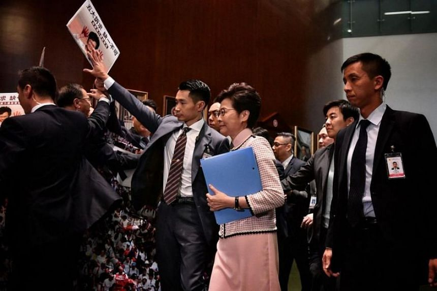 Hong Kong Chief Executive Carrie Lam arrives to deliver her annual policy address, as lawmakers hold signs and shout protests, at the Legislative Council in Hong Kong on Oct 16, 2019.