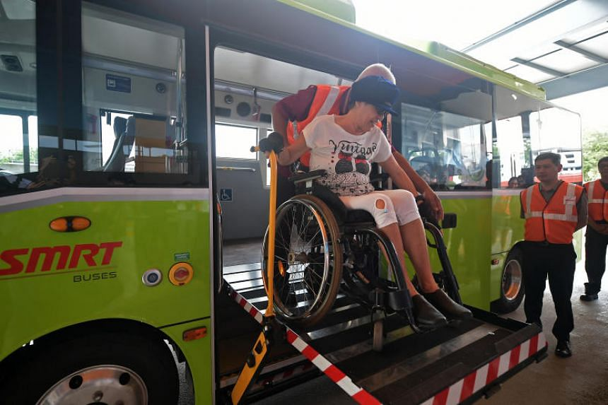 Ms Wendy Tan, a wheelchair user, being helped onto an 825 bus during a media preview of the new expanded Yio Chu Kang Bus Interchange on Oct 16, 2019.