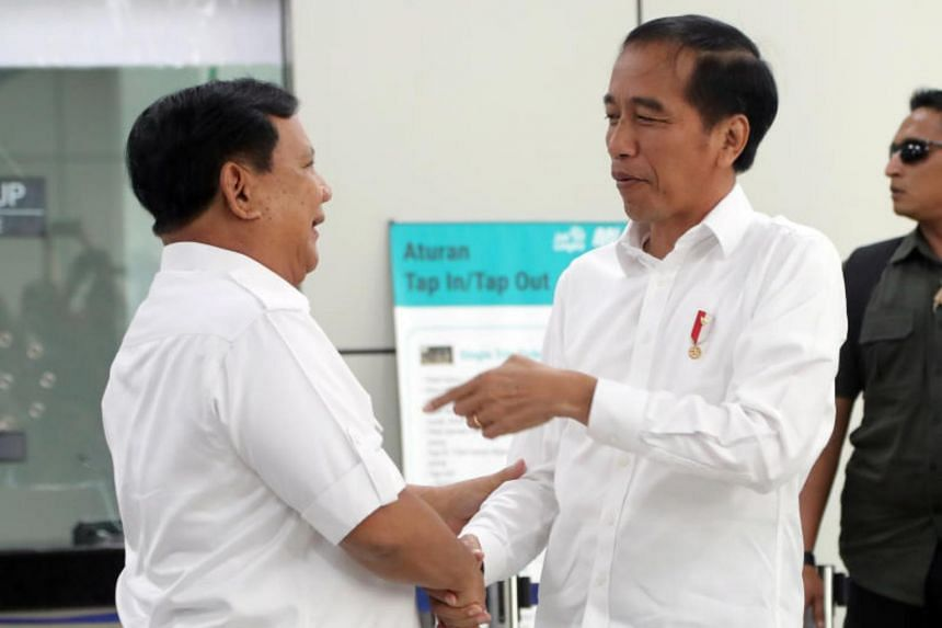 In a photo taken on July 19, Indonesian President Joko Widodo (right) shakes hands with defeated rival Prabowo Subianto during their meeting on a train in Jakarta.