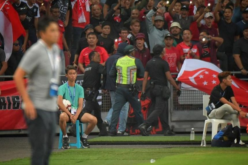 A pitch invader (in hoodie) being taken away by security personnel after he went to the Uzbekistan stands and taunted fans during the World Cup qualifier between Singapore and Uzbekistan on Oct 15, 2019.