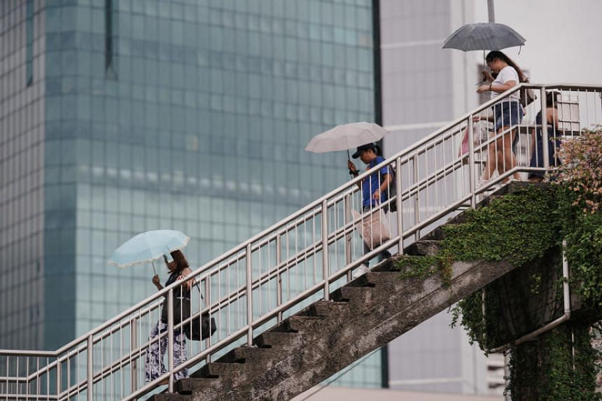 People are seen carrying umbrellas to shield against the rain in Novena on Sept 29, 2019.