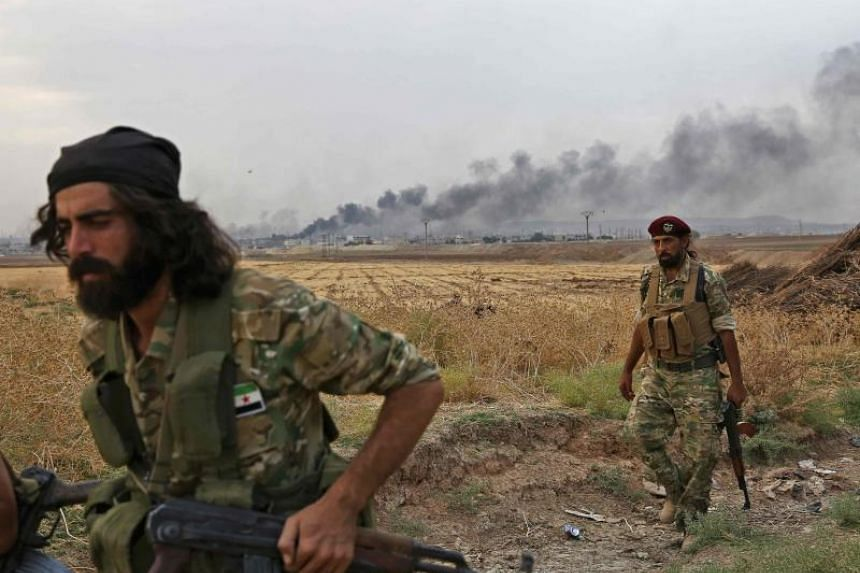 Turkey-backed Syrian fighters man a position across the key north-eastern Syrian border town of Ras al-Ain as smoke billows above it on Oct 16, 2019.