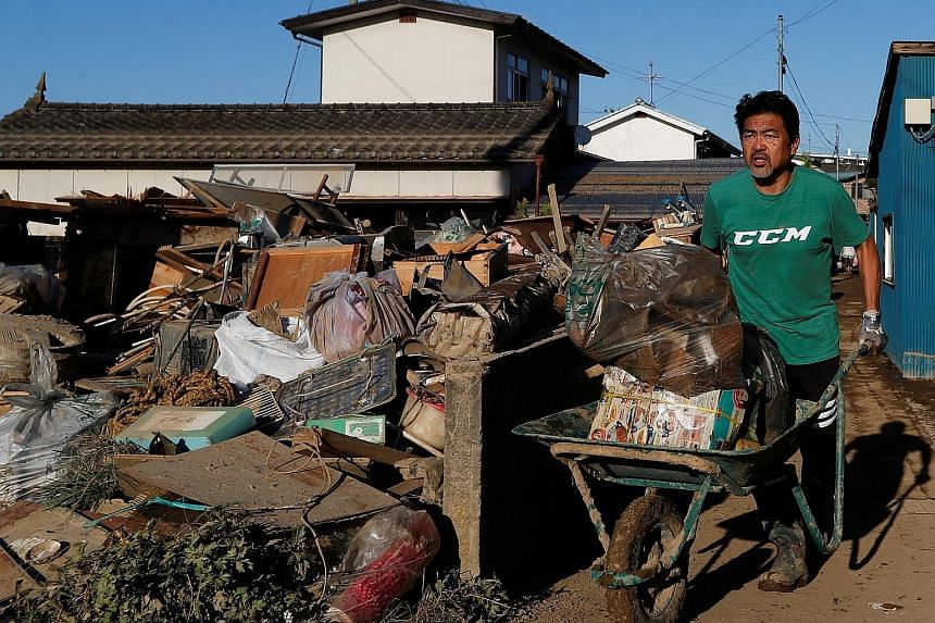 A man clearing debris yesterday in the aftermath of Typhoon Hagibis in Yanagawa, Fukushima prefecture, in Japan. PHOTO: REUTERS