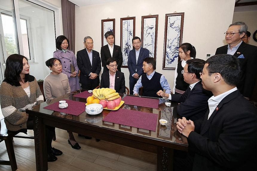 Deputy Prime Minister Heng Swee Keat visiting a family yesterday in Seasons Garden, a residential project by Keppel Land China in Tianjin Eco-city, accompanied by Mr Zhang Yuzhuo (seated, second from right), Party Secretary of the Tianjin Binhai New