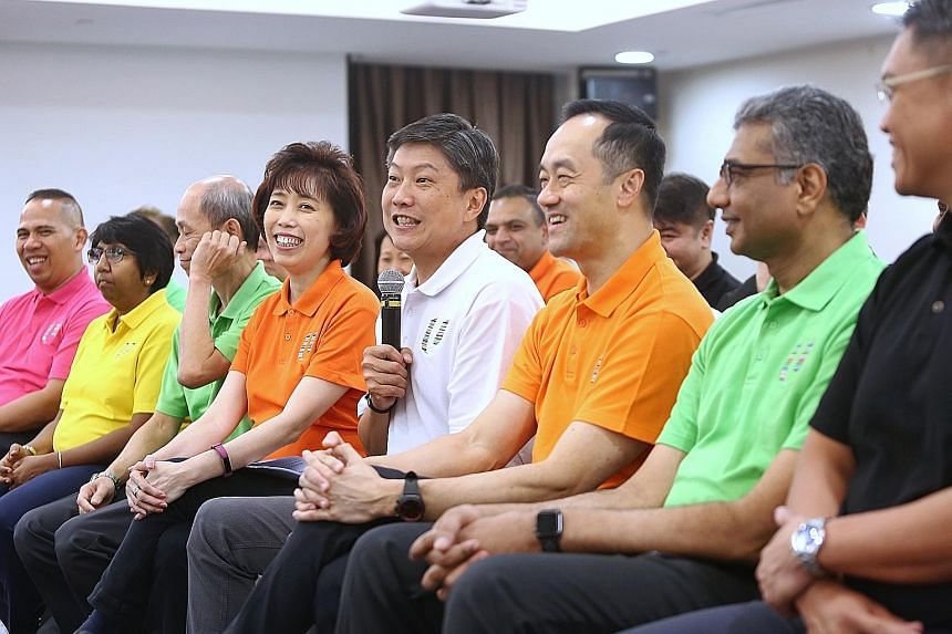 NTUC secretary-general Ng Chee Meng (in white) at a media briefing yesterday with the new NTUC central committee members. They are (from left) vice-presidents Abdul Samad Abdul Wahab, K. Thanaletchimi and Ong Hwee Liang; president Mary Liew; deputy s