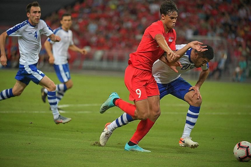 Ikhsan Fandi, who scored in the 3-1 loss to Uzbekistan, challenging for the ball during the World Cup 2022 qualifier at the National Stadium on Tuesday. Singapore, fourth in Group D with four points, will have to finish top or among the four best run