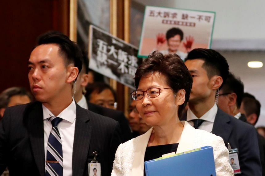 Chief Executive Carrie Lam arrives to answer questions from lawmakers regarding her policy address, as pro-democracy legislators hold up placards behind her, at the LegCo in Hong Kong, on Oct 17, 2019.