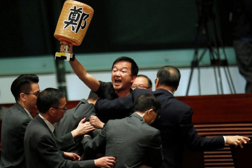 A pro-democracy lawmaker is escorted by security from the Legislative Council, as Hong Kong's Chief Executive Carrie Lam takes questions from lawmakers regarding her policy address, in Hong Kong, on Oct 17, 2019.