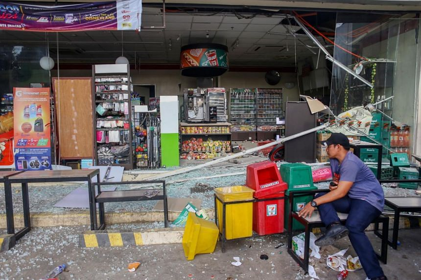 A store owner guards the remains of his store after a 6.4-magnitude earthquake hit the night before in the city of Digos, Davao del Sur province on the southern Philippine island of Mindanao on Oct 17, 2019.