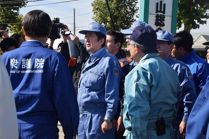 Japanese Prime Minister Shinzo Abe inspects an area hit by Typhoon Hagibis during a visit to Fukushima and Miyagi prefectures on Oct 17, 2019.