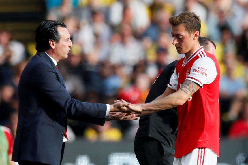 Arsenal's Mesut Ozil (right) shakes hands with manager Unai Emery after being substituted off during the English Premier League match between Watford and Arsenal on Sept 15, 2019.