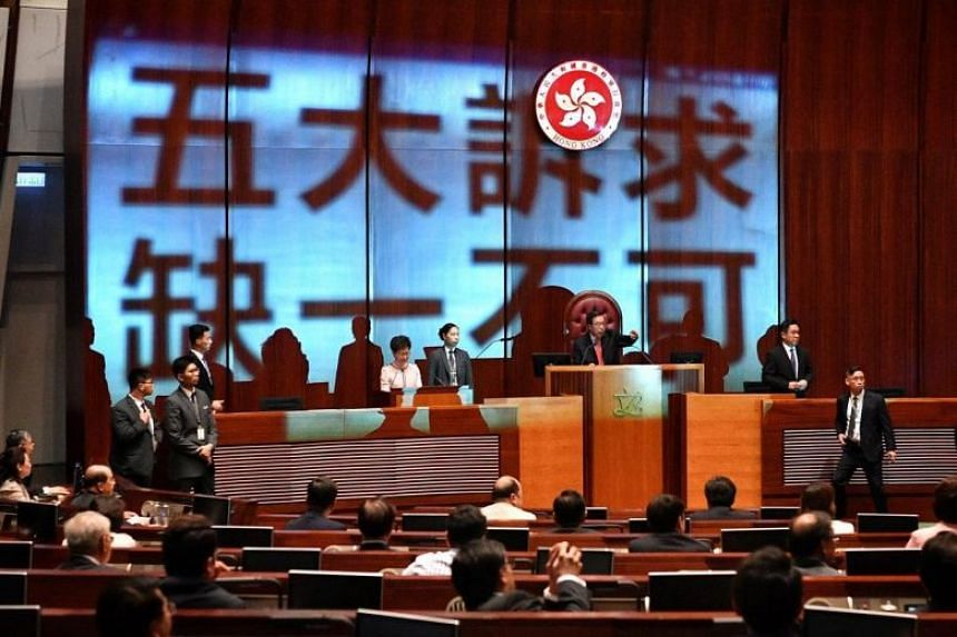 """Pro-democracy legislators project the words """"five demands, not one less"""" on Carrie Lam before she was able to address the Legislative Council on Oct 16, 2019."""