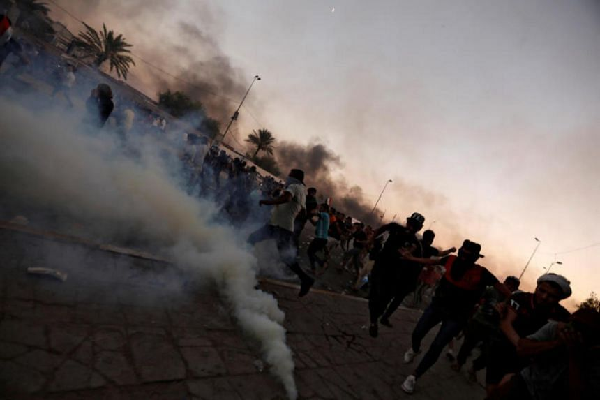 Demonstrators disperse as Iraqi security forces use tear gas during a protest in Baghdad, Iraq, on Oct 5, 2019.