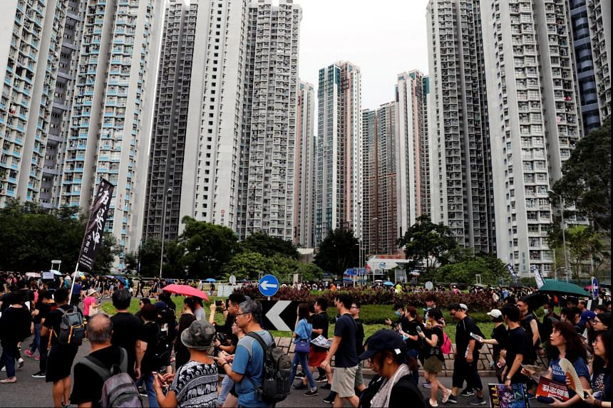 Anti-extradition Bill protesters march against the backdrop of residential buildings in Tseung Kwan O, Hong Kong, on Aug 4, 2019. The government has announced new policies to ease the city's housing crisis.
