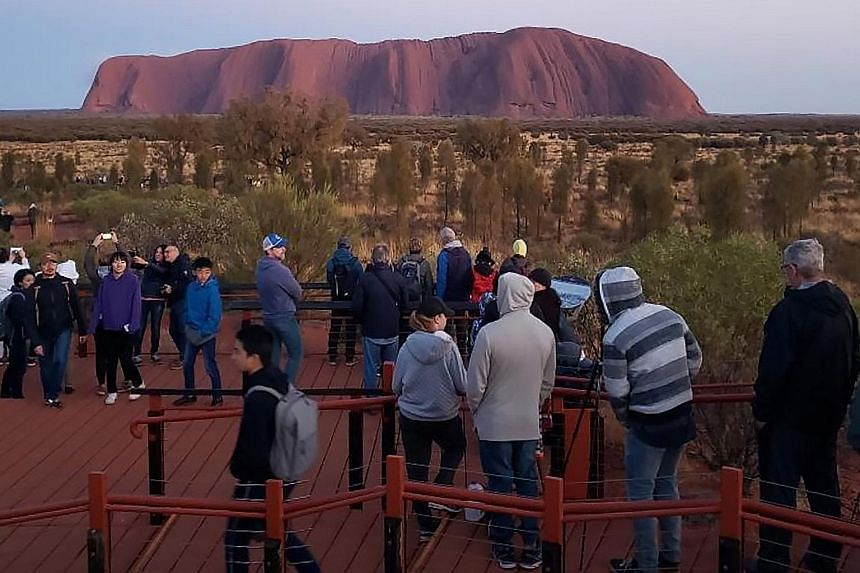 Tourists viewing Uluru in Australia's Northern Territory. Recently, visitors have been rushing to climb the rock, ahead of a ban set to take effect on Oct 26.