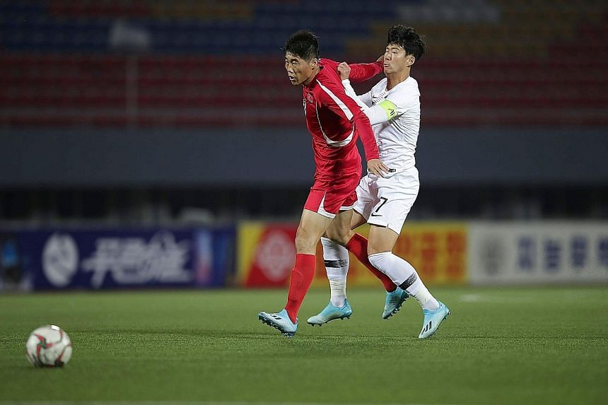 North Korea's Ri Yong Chol holding off South Korea's captain Son Heung-min during a tepid World Cup 2022 qualifier in Pyongyang. The two neighbours played out a goal-less draw in front of an empty stadium without a live broadcast. PHOTO: AGENCE FRANC