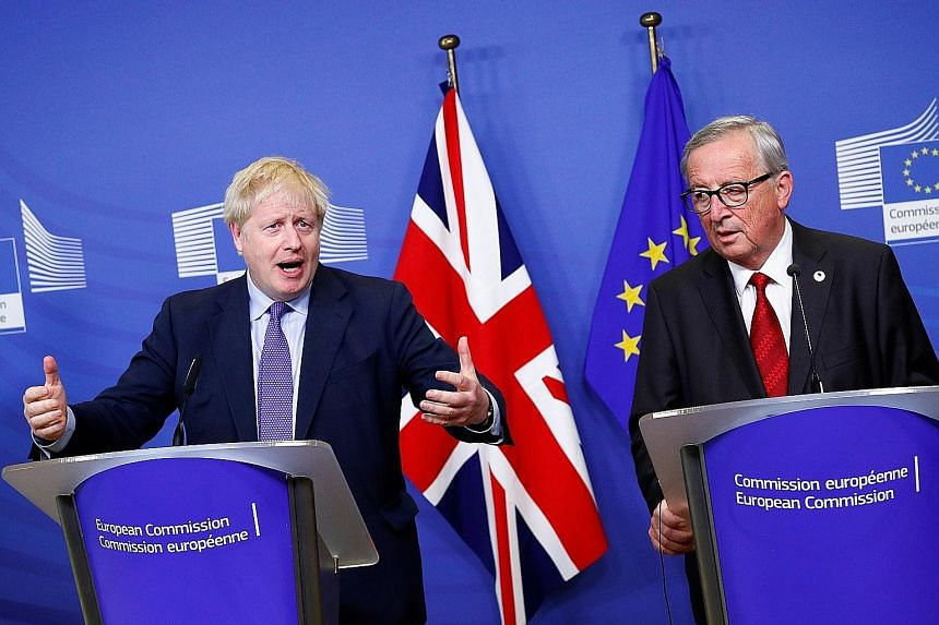 British Prime Minister Boris Johnson (left) and European Commission President Jean-Claude Juncker attending a news conference in Brussels yesterday after agreeing on the Brexit deal.