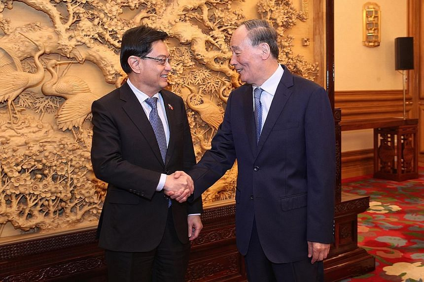 Deputy Prime Minister Heng Swee Keat (left) meeting Chinese Vice-President Wang Qishan in Beijing yesterday as part of his four-day visit to China that also took him to Chongqing and Tianjin. PHOTO: MCI