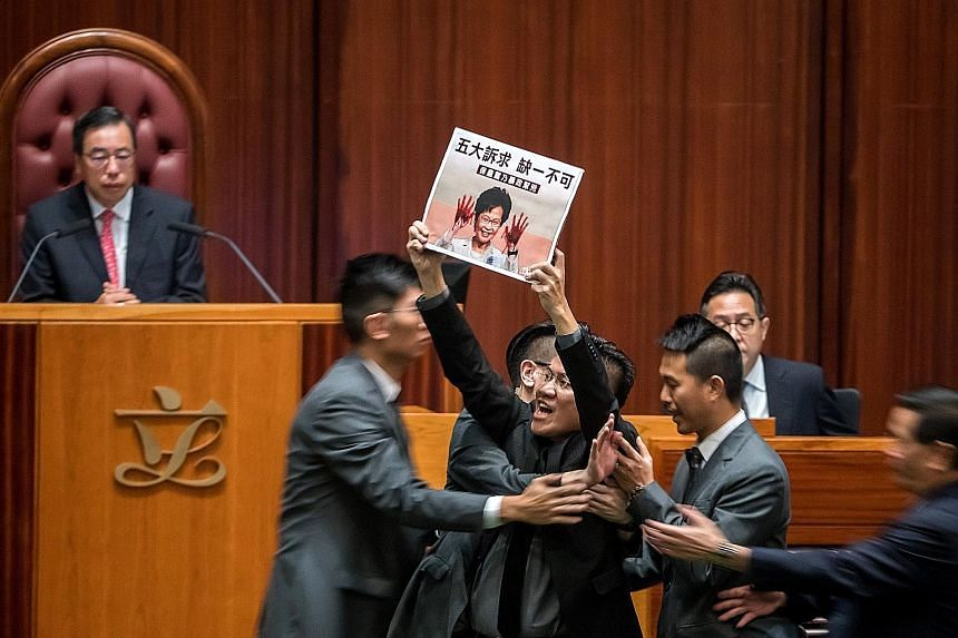 Above: Chief Executive Carrie Lam arriving for a question-and-answer session at the Legislative Council in Hong Kong yesterday amid noisy protests from pro-democracy lawmakers. Right: Lawmaker Gary Fan protesting during the Legislative Council sessio
