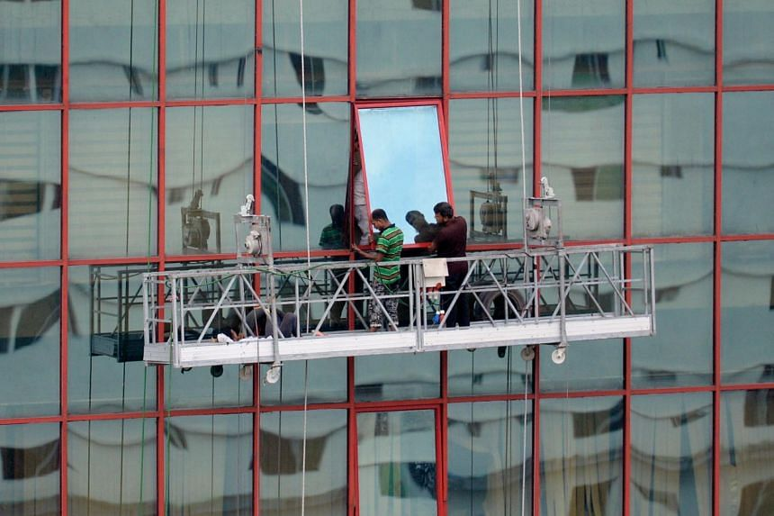 Bangladeshi workers fix a glass window onto a high rise building in Dhaka on Sept 4, 2019.