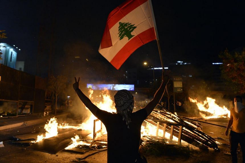 Protesters cut off roads and burned debris in downtown Beirut, Lebanon, on Oct 17, calling for politicians to step down and hold early elections.