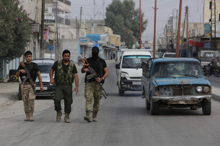 Turkish-backed Syrian fighters walk down a street in the Syrian border town of Tal Abyad on Oct 17, 2019, as Turkey and its allies continue their assault on Kurdish-held border towns in north-east Syria.