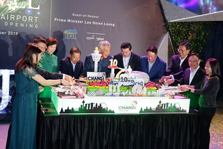 Prime Minister Lee Hsien Loong is flanked by Changi Airport Group chairman Liew Mun Leong and Changi Airport Group CEO Lee Seow Hiang and other guests during a cake-cutting segment to celebrate Changi Airport Group's 10th year anniversary at Jewel