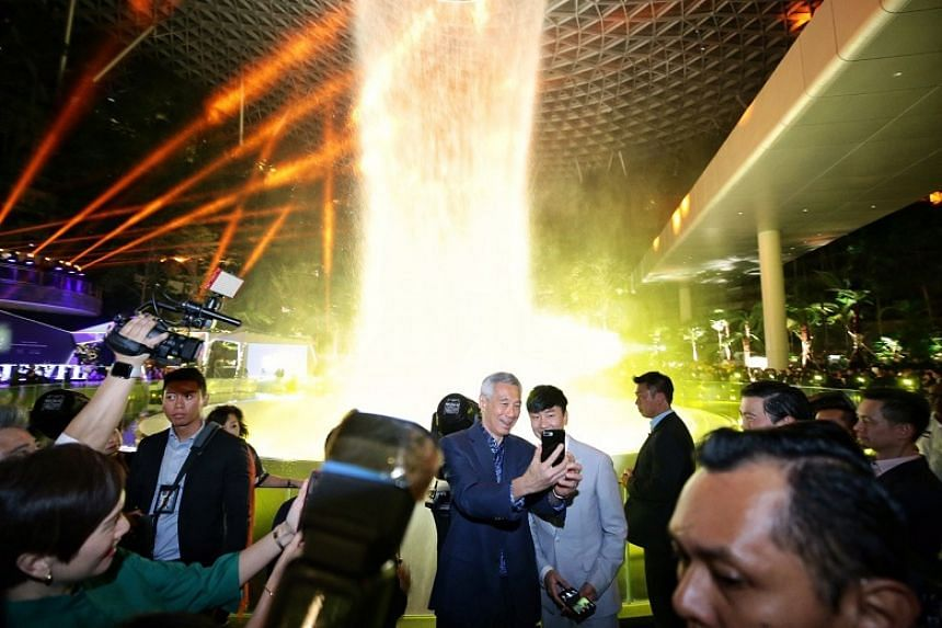 Prime Minister Lee Hsien Loong taking a selfie with JJ Lin during a light and sound show at the official opening of Jewel Changi Airport on Oct 18, 2019