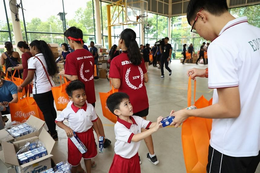 Chin Tze Young (centre) and Abdul Atif (left) from Cherry Kidz Montessori School were the youngest of 700 volunteers who prepared gift packs for beneficiaries on Oct 18, 2019.