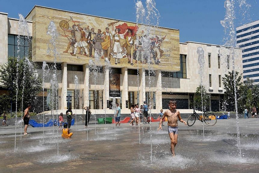 Children cooling off at the Skanderbeg Square in the Albanian capital of Tirana in August, amid a heatwave in Europe. Global warming is increasing the likelihood of more frequent and intense extreme weather events.