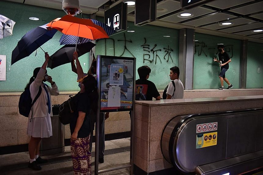 Protesters obscuring a security camera with umbrellas as another spray-painted graffiti at an MTR station yesterday.