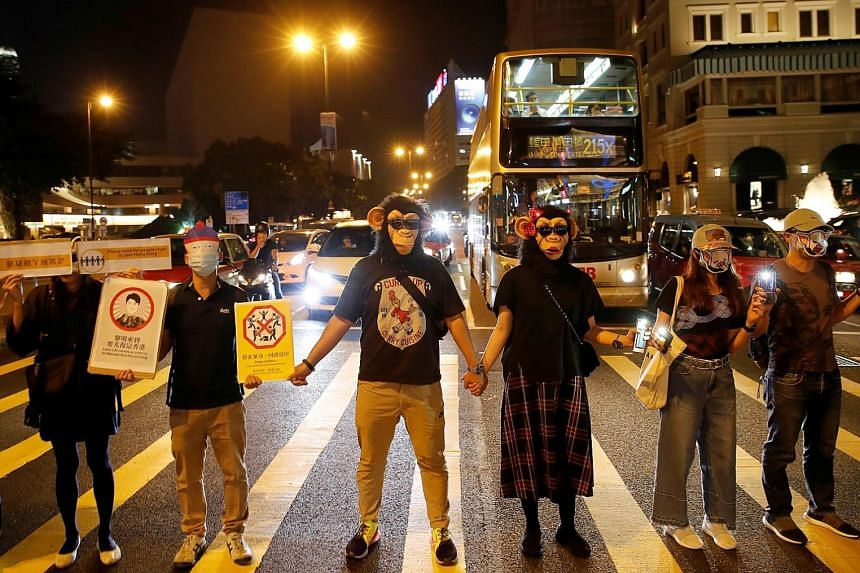 Protesters standing in a human chain which formed across Hong Kong yesterday along the city's metro route, with many wearing masks despite a ban on covering faces at public rallies. In another show of defiance, pro-democracy campaigners are planning