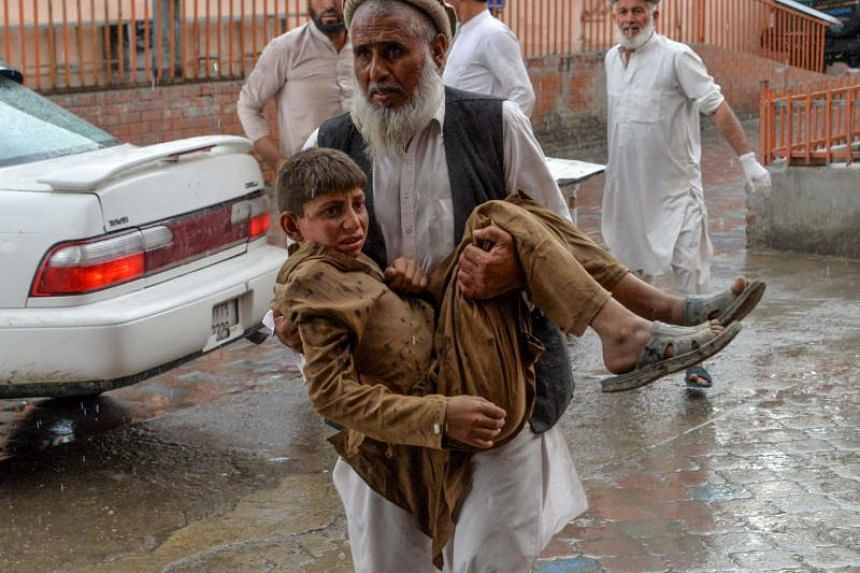 A volunteer carries an injured youth to hospital, following a bomb blast in Haska Mina district of Nangarhar Province on Oct 18, 2019.