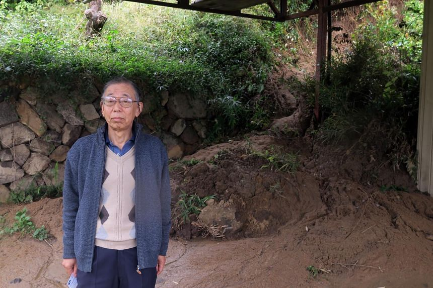 Retiree Katsushi Okazaki, 71, who lives on a hill overlooking Marumori, stands next to a small mudslide that nearly caused damage to his backyard.