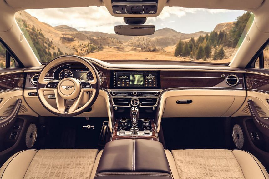 """The Flying Spur is low, sporty and graceful, and its performance is nothing short of phenomenal. Its button-heavy cockpit has a new """"B"""" design motif. There is leather upholstery in a 3D interlaced pattern and the retractable """"Flying B"""" mascot"""